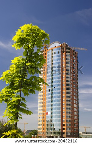 Green tree and growing building - stock photo