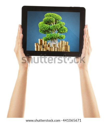 Green tree in bag with a dollar sign in screen of tablet isolated on white - stock photo
