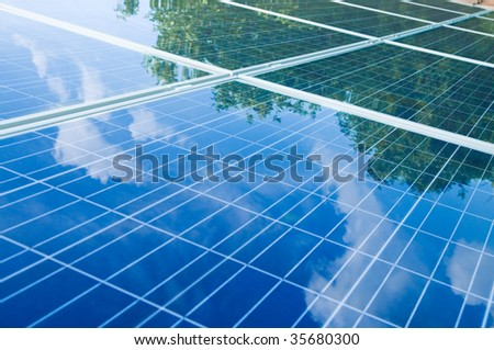Green trees and blue sky reflection on solar panels. Go green with renewable energy!