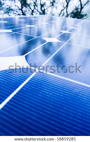 Green trees and blue sky reflection on solar panels. Go green with renewable energy! - stock photo