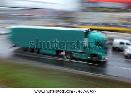 Green truck in the city on a deliberately blurred background