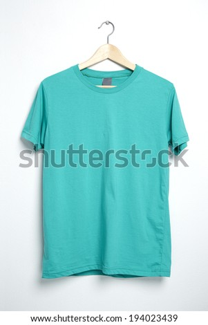 Green tshirt template on hanger ready for your own graphics. - stock photo