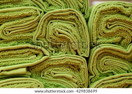 Green twisted terry towels stacked on each other - stock photo
