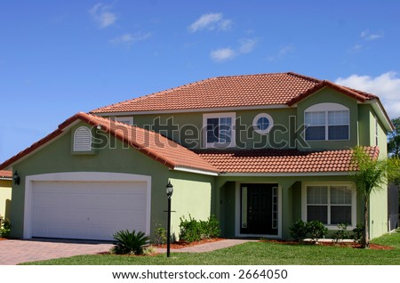 green two story new construction home against blue sky - stock photo