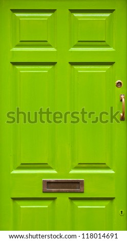 green typical residential house door in Ireland (golden lock, handle and mailbox) - stock photo