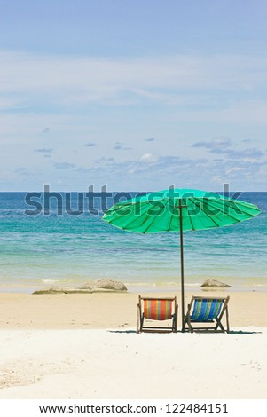 Green umbrella and chair on beach with clear sky