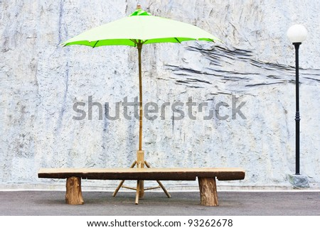 Green umbrella on the wooden bench in front of the park.