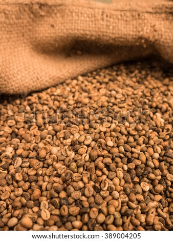 green unroasted coffee beans in sack.