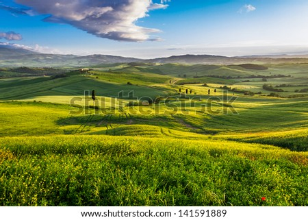Green valley and mountains at sunset in Tuscany - stock photo