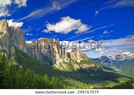 Green valley sided by rocky cliffs of Catinaccio massif, Dolomite Alps, Italy