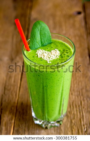 Green vegetable and herbs smoothie with heart of sesame seeds. Love for a healthy raw food concept. - stock photo