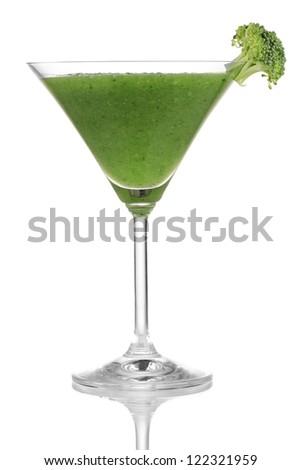 Green vegetable juice in coctail glass isolated on white