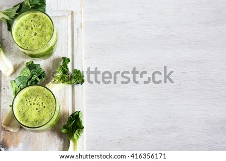 Green vegetable smoothie in jar and ingredients on the white wooden background. Diet concept with text space. Detox. Vegetarian food - stock photo