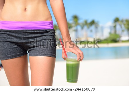 Green vegetable smoothie. Woman living healthy lifestyle drinking vegetable smoothies after fitness running workout on summer day. Beautiful fit sports model eating healthy. - stock photo