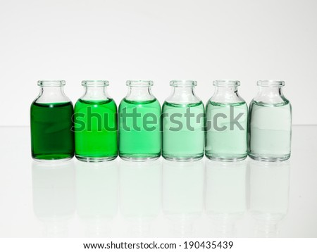 Green Vials Gradient. Several vials on a glass table top with different tones of green from clear to dark green. - stock photo