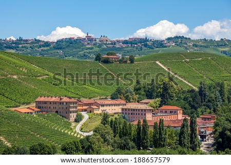 Green vineyards on the hills and winery complex in Piedmont, Northern Italy. - stock photo