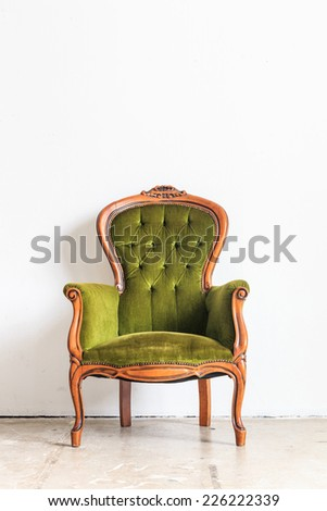 Green vintage armchair on white wall.