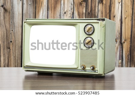Green vintage television with old wood wall.