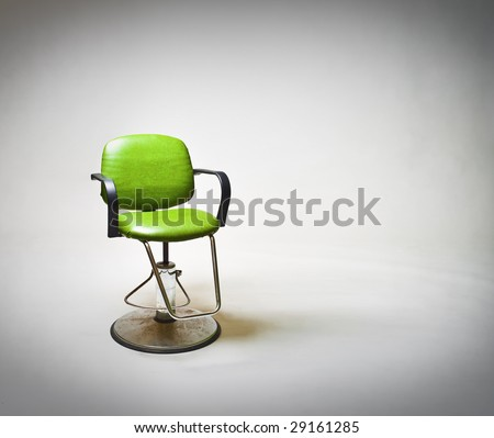 Green vintage vinyl covered barbershop or beauty salon chair against large white backdrop. Lots of copy space to right. - stock photo