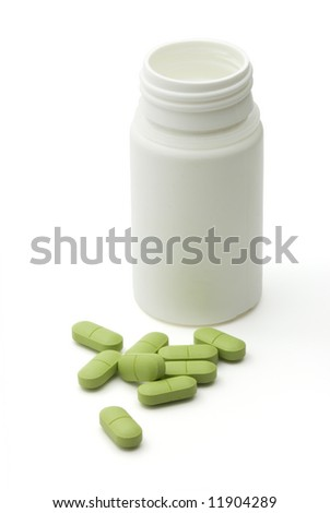 Green vitamin pills with dose on white background - stock photo