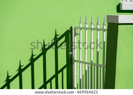 green wall with shadow of white metal fence on it.