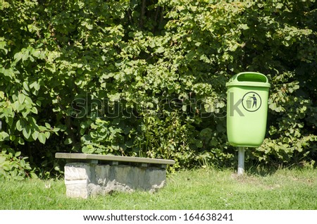 Green waste bin in a park with a park bench - stock photo
