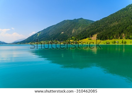 Green water Weissensee lake in Alps Mountains, Austria - stock photo