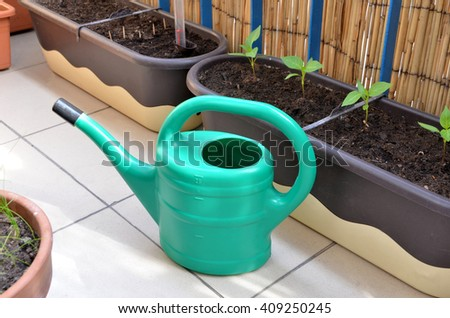 Green watering can and seedlings in flower boxes as a part of urban garden on the balcony - stock photo
