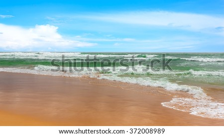 Green wave with white sea foam on sandy paradise beach. - stock photo