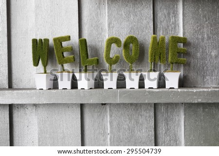 Green welcome sign against silver painted wooden wall - stock photo