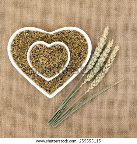 Green wheat feekeh in heart shaped bowls with fresh ears over hessian background. - stock photo