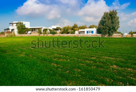 Green wheat field near the village houses and the sky with clouds. - stock photo