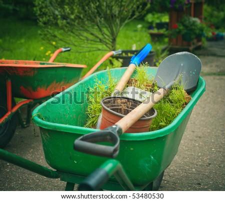 Green wheelbarrow standing in the garden - stock photo