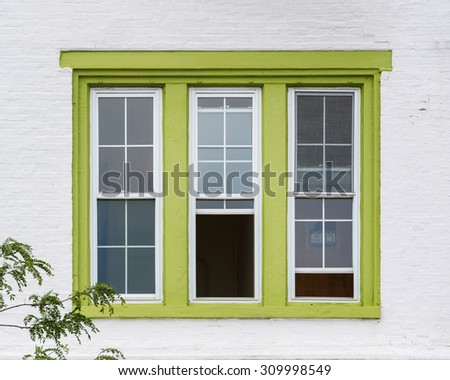 Green window frame against white wall on Market Space in Annapolis, Maryland