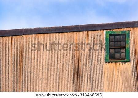 Green window on metal against blue sky - stock photo