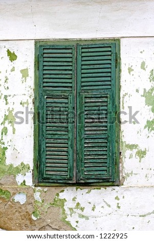 green window shutters and faded wall