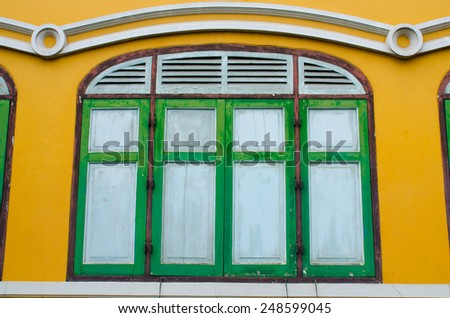 green windows on yellow wall - stock photo