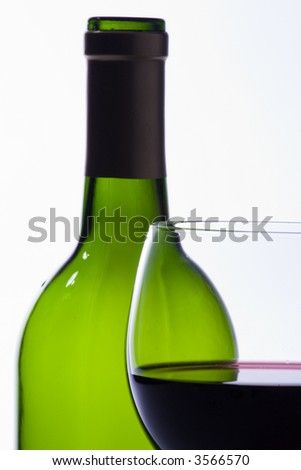 Green wine bottle and glass of red wine, over white - stock photo