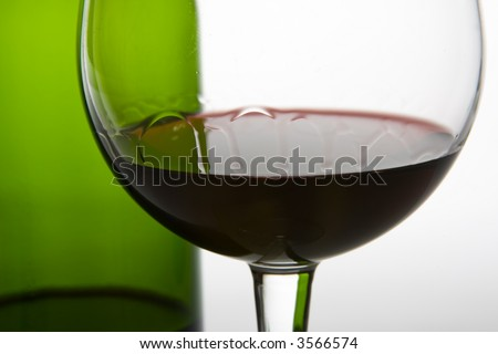 green wine bottle and red wine legs - stock photo