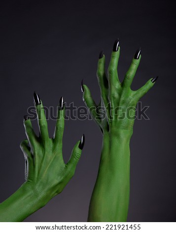 Green witch hands with black nails stretching up, Halloween theme, studio shot on black background  - stock photo