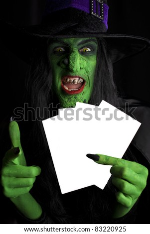 Green witch with space for text, black background. - stock photo