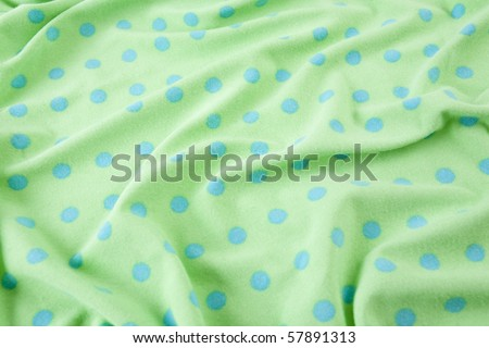 Green with blue polka dots wrinkled fabric - stock photo