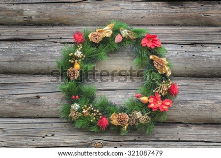Green with red and golden Christmas conifer wreath at old log cabin wall background - stock photo