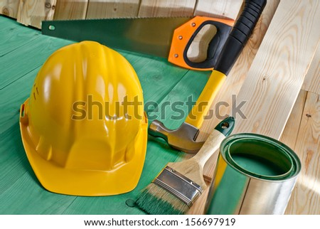 green wood floor with a helmet, hammer, brush and paint - stock photo