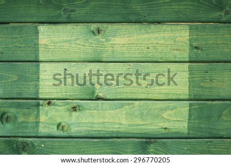 Green wooden background with light green square on it. - stock photo