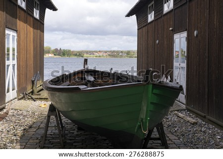 Green wooden boat close to wooden shipyard in Middelfart, Denmark - stock photo