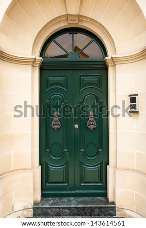 green wooden front door to the house in the Mediterranean