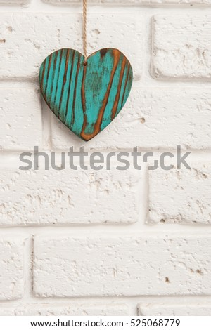 Green wooden heart on a white brick wall background
