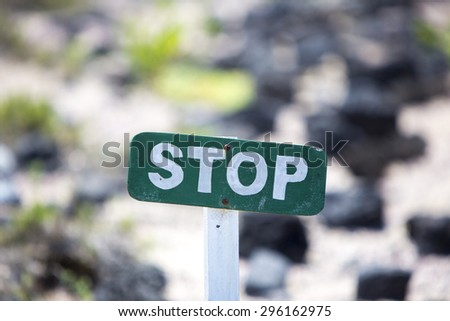 Green wooden stop sign laying in the rocks at the beach to protect the nature. Galapagos Islands, Ecuador 2015. - stock photo