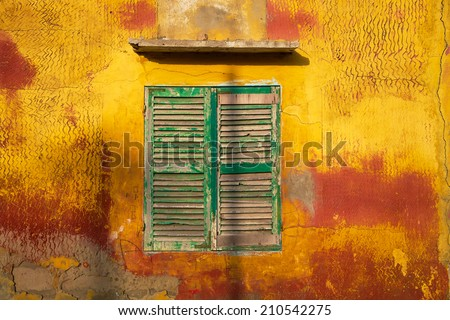 Green wooden window and old vintage orange house in Saint Louis, Senegal - stock photo